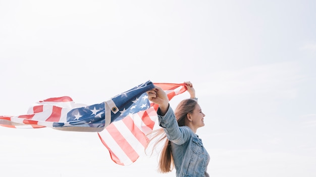 Mujer sonriendo y sosteniendo una bandera estadounidense ancha y alta en el cielo