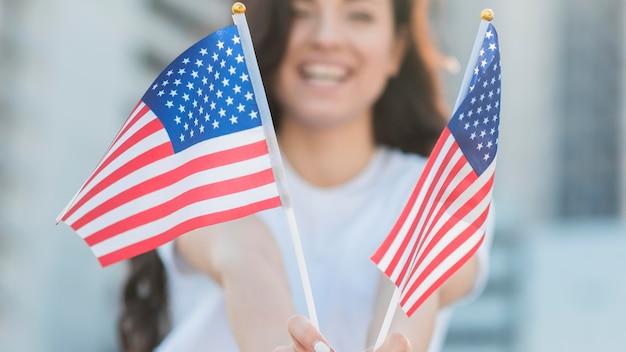 Mujer sonriendo y sosteniendo banderas de estados unidos