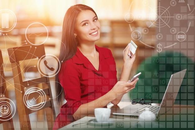 Mujer sonriendo con una tarjeta y un móvil