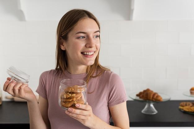 Mujer sonriente abriendo un frasco con galletas