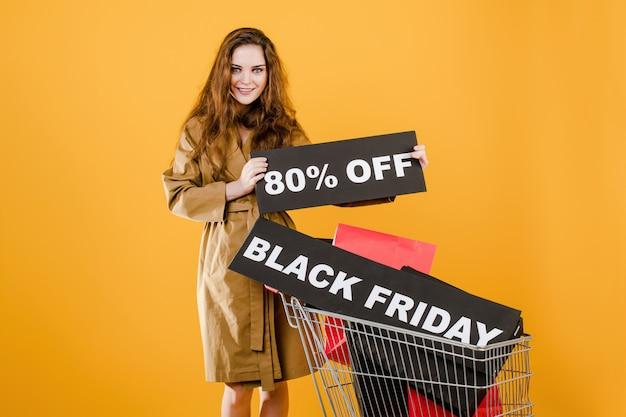 Mujer sonriente en abrigo de otoño con viernes negro 80% signo y coloridas bolsas de compras en carro aislado sobre amarillo