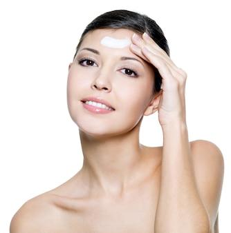 Mujer sonriente adulta joven hermosa que aplica la crema cosmética en la frente.