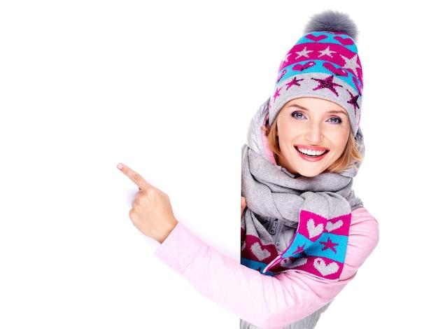 Mujer sonriente adulta en ropa de abrigo de invierno sostiene el cartel blanco en las manos y señala