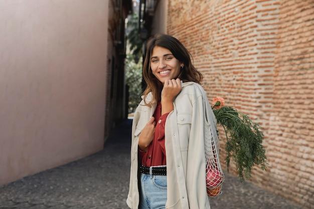 Mujer sonriente afuera con bolsas de la compra.