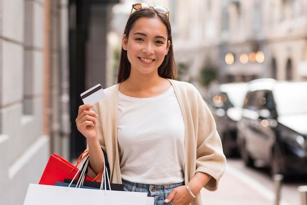 Mujer sonriente afuera sosteniendo bolsas de compras y tarjeta de crédito