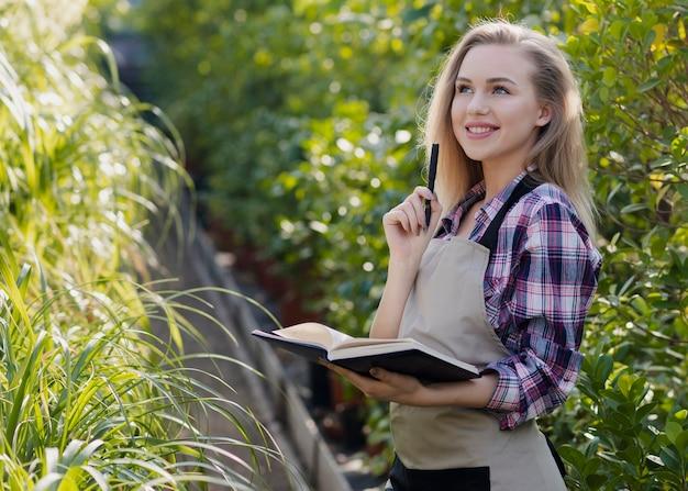 Mujer sonriente con agenda en invernadero