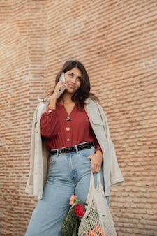 Mujer sonriente al aire libre con bolsas de la compra y smartphone