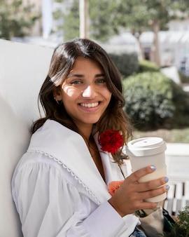 Mujer sonriente al aire libre con flores y taza de café