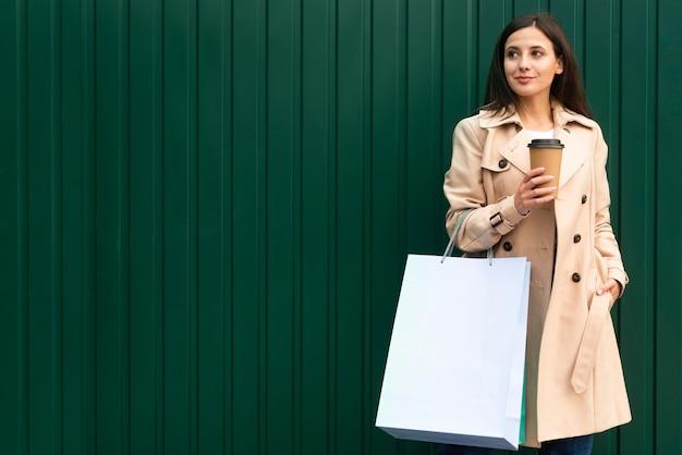 Mujer sonriente al aire libre tomando café y sosteniendo bolsas de la compra.