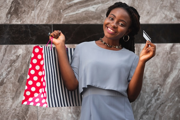 Mujer sonriente de ángulo bajo con bolsas de compras