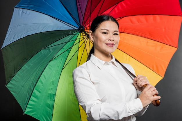 Mujer sonriente de ángulo bajo con coloridos paraguas