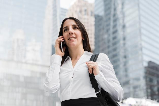 Mujer sonriente de ángulo bajo hablando por teléfono