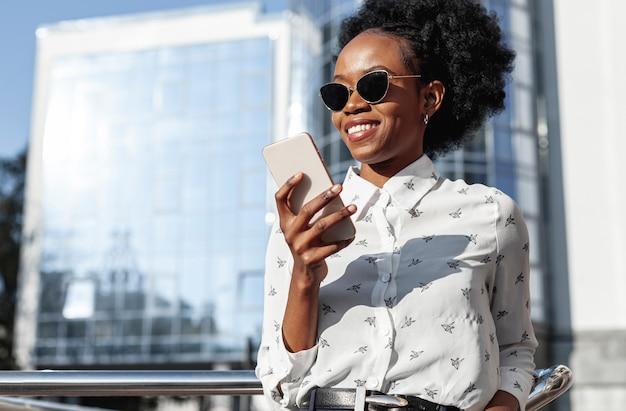 Mujer sonriente de ángulo bajo mirando el teléfono