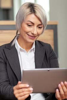 Mujer sonriente de ángulo bajo en tableta