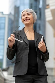 Mujer sonriente de ángulo bajo con traje