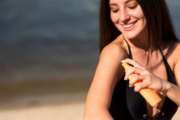 Mujer sonriente aplicando protector solar en la playa.