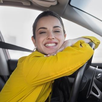 Mujer sonriente apoyándose en el volante