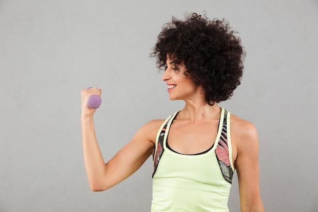 Mujer sonriente de la aptitud que hace ejercicio con pesa de gimnasia en estudio