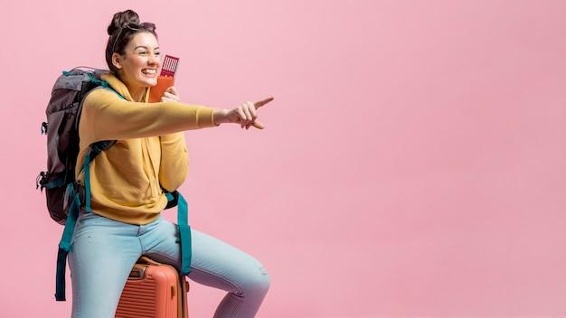 Mujer sonriente apuntando delante de ella con espacio de copia