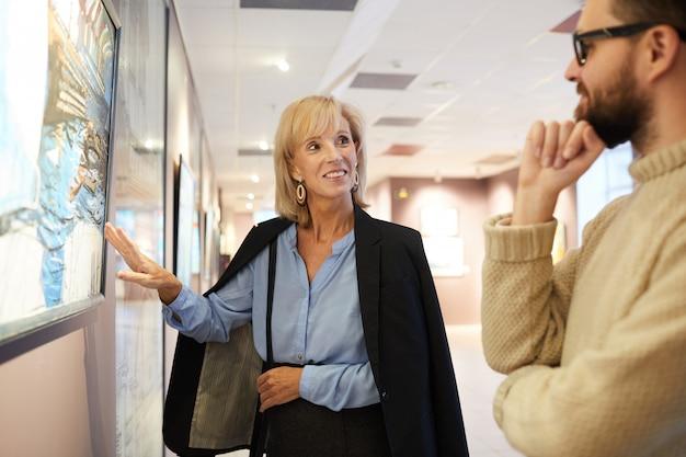 Mujer sonriente apuntando a la pintura en la galería de arte