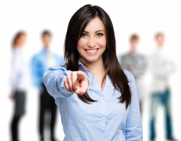 Mujer sonriente apuntando su dedo hacia ti