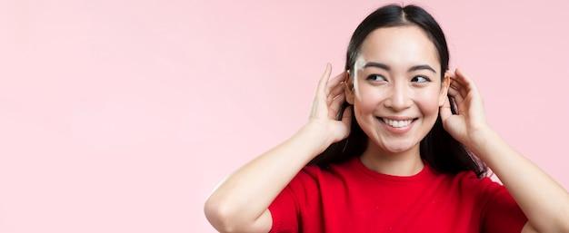 Mujer sonriente arreglando su cabello