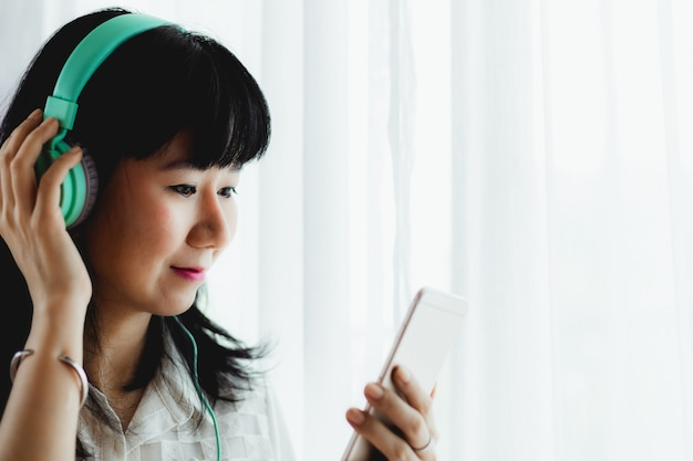 Mujer sonriente asiática con auriculares, escuchar música y usar el teléfono inteligente para el entretenimiento y el ocio en el concepto de hogar