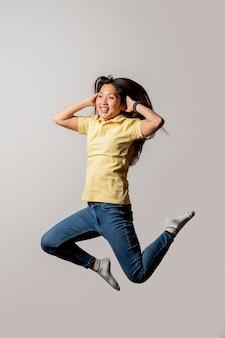 Mujer sonriente asiática que salta en estudio