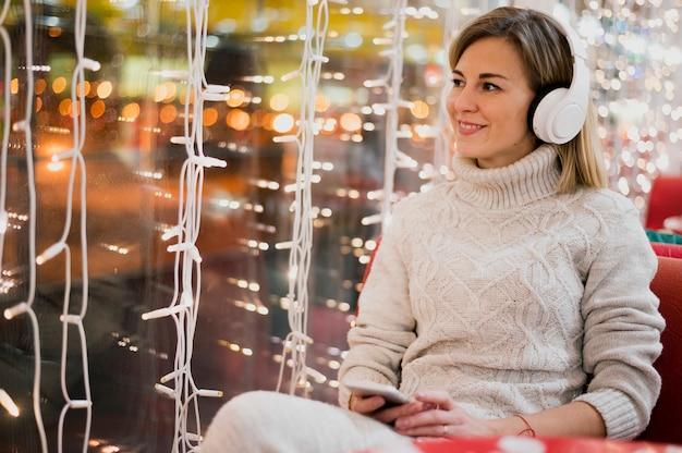 Mujer sonriente con auriculares cerca de luces de navidad