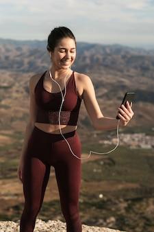 Mujer sonriente con auriculares mirando móvil
