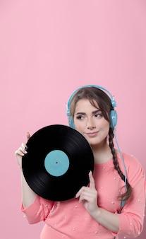 Mujer sonriente con auriculares posando con disco de vinilo