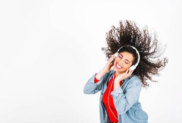 Mujer sonriente en auriculares sacudiendo el pelo