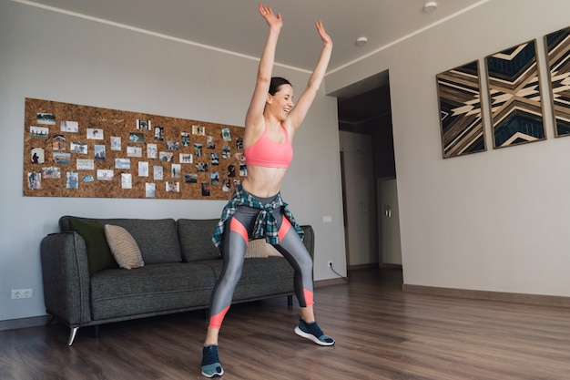 Mujer sonriente bailando en medio de la sala de estar disfrutando de ella y la vida