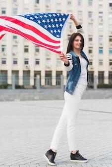 Mujer sonriente con bandera americana en la ciudad