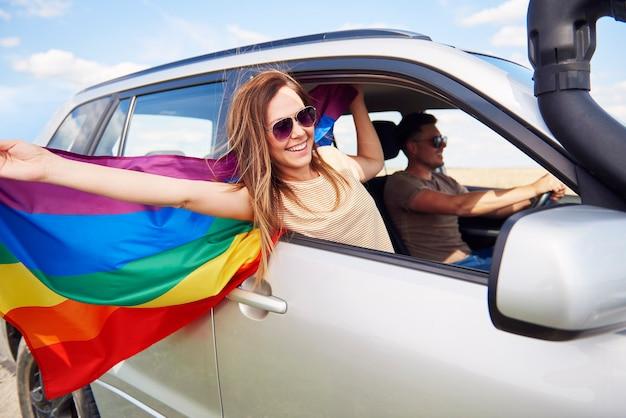 Mujer sonriente con bandera del arco iris viajando en coche en verano