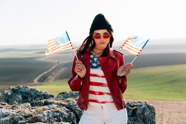 Mujer sonriente con banderas americanas posando en la cima de la montaña