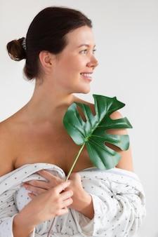 Mujer sonriente en bata de baño con hoja