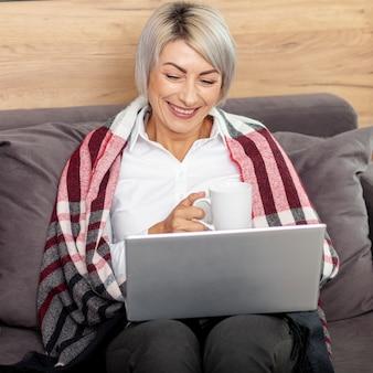 Mujer sonriente bebiendo café y trabajando