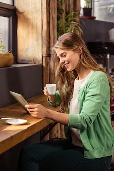 Mujer sonriente bebiendo café y usando tableta