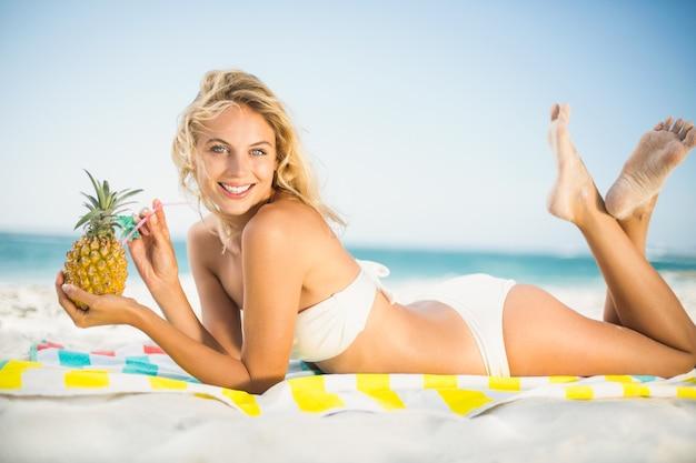 Mujer sonriente bebiendo de una piña