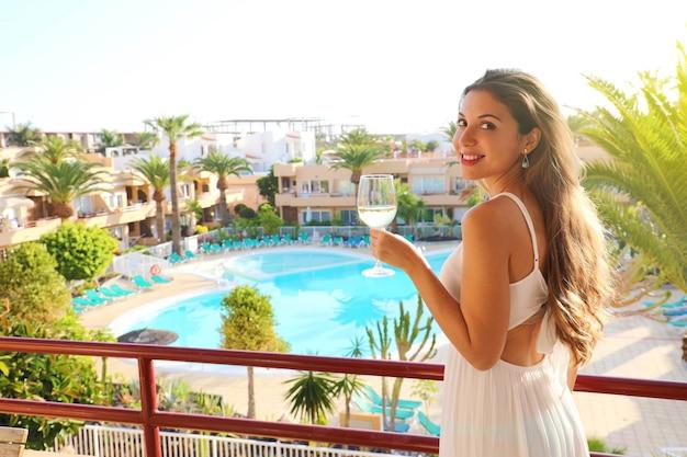 Mujer sonriente bebiendo vino blanco en la terraza del resort al aire libre