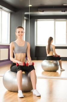 Mujer sonriente con la bola y pesas de gimnasia del ejercicio en gimnasio.