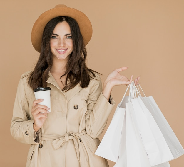 Mujer sonriente con bolsas de compras y café