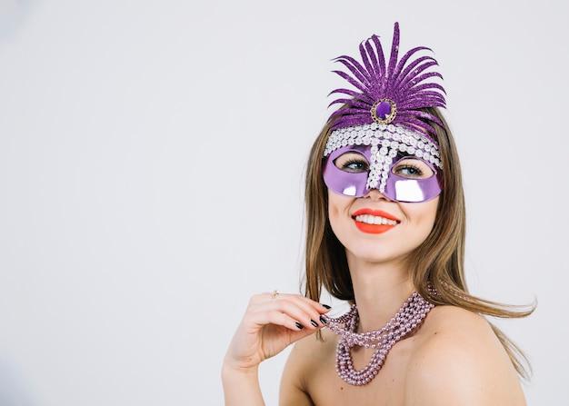 Mujer sonriente bonita que lleva la máscara decorativa púrpura del carnaval en el fondo blanco