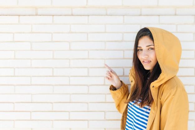 Mujer sonriente bonita que señala en la pared de ladrillo blanca
