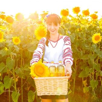 Mujer sonriente en el bordado que sostiene una cesta con aceite de girasol en un campo