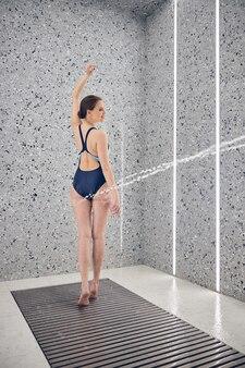 Mujer sonriente con un brazo levantado de pie sobre una alfombra antideslizante durante el procedimiento de spa