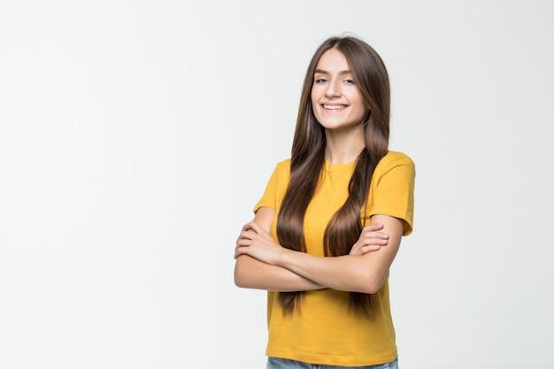 Mujer sonriente con los brazos cruzados aislados en la pared blanca.