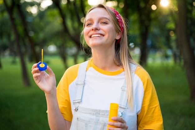 Mujer sonriente con burbujas al aire libre