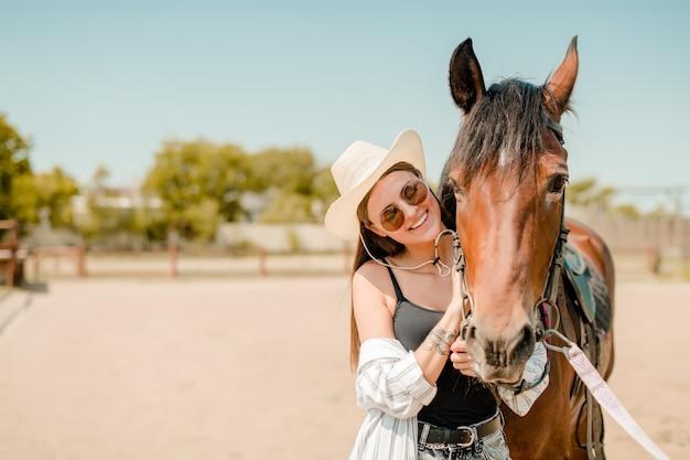 Mujer sonriente con un caballo en un rancho occidental